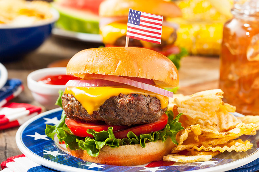 Photo of hamburger and chips with an American flag on top.